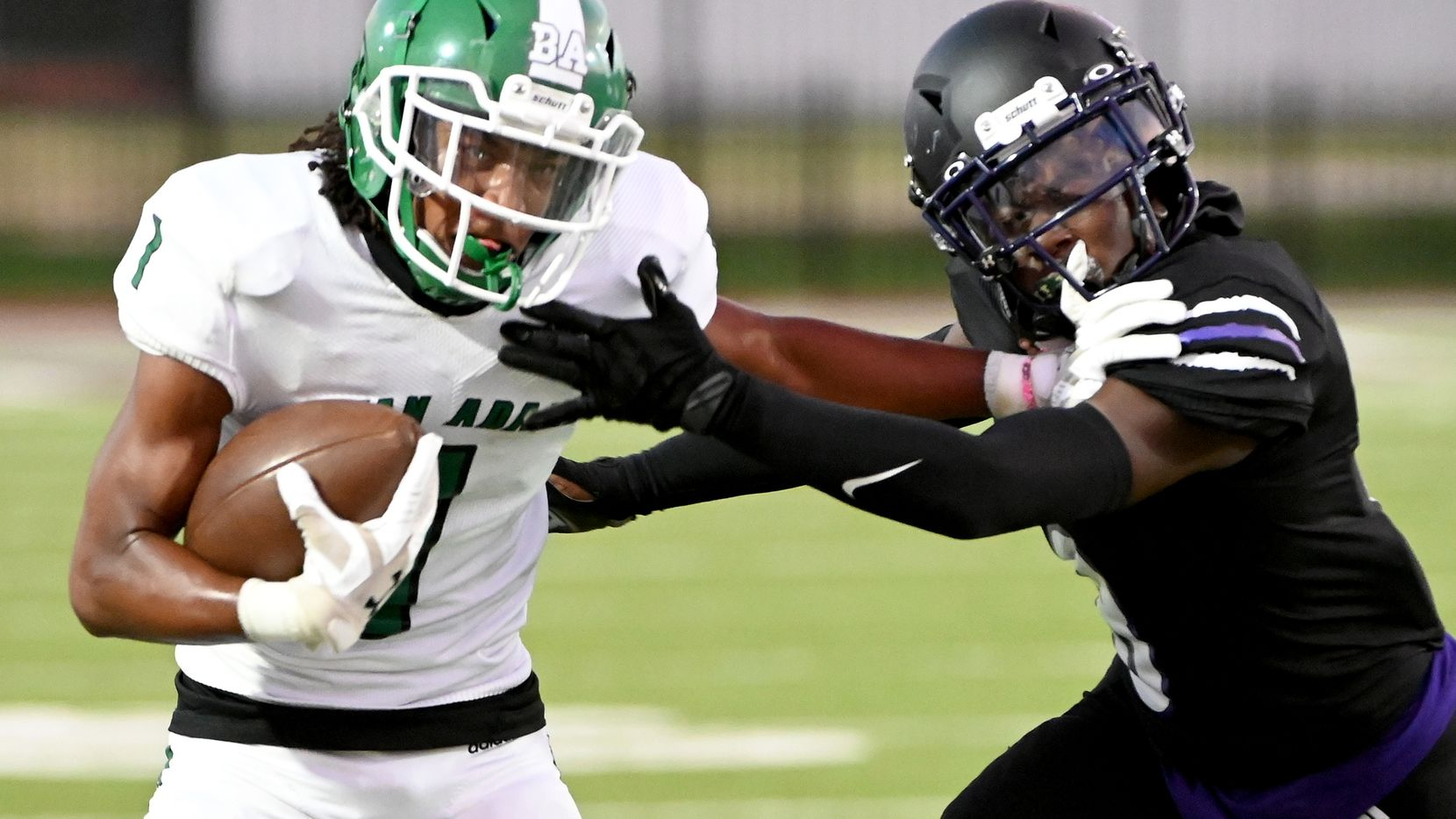 Bryan Adam's Rishon Taylor (1) stiff arms Lincoln's Donnell Williams (8) in the first half during a high school football game between Bryan Adams and Lincoln , Friday, Sept. 3, 2021, in Dallas.