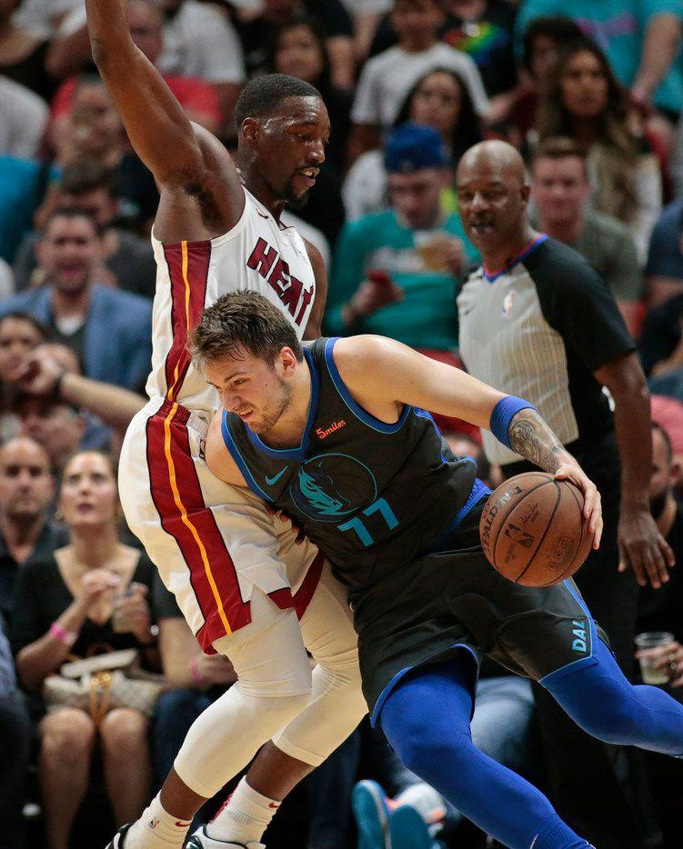 Dallas Mavericks forward Luka Doncic (77) drives against Miami Heat center Bam Adebayo (13) during the second half of an NBA basketball game, Thursday, March 28, 2019, in Miami. (AP Photo/Joel Auerbach)