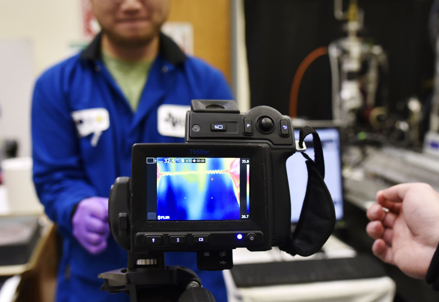Research scientist Jiuke Mu holds a piece of rubber and twists the fibers to cool them down. With the use of a thermographic camera he shows the cooling at the Nano Tech Institute lab on the campus of UTD in Richardson on Oct. 24, 2019.