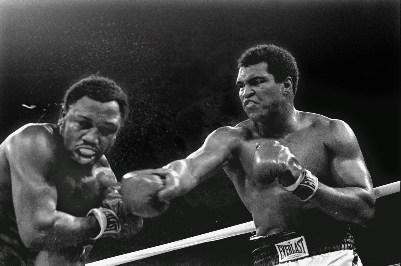 In this Oct. 1, 1975 file photo, sweat spray flies from the head of challenger Joe Frazier as heavyweight champion Muhammad Ali connects with a right in the ninth round of their heavyweight title fight in Manila, Philippines. Ali won the fight on a decision to retain the title.