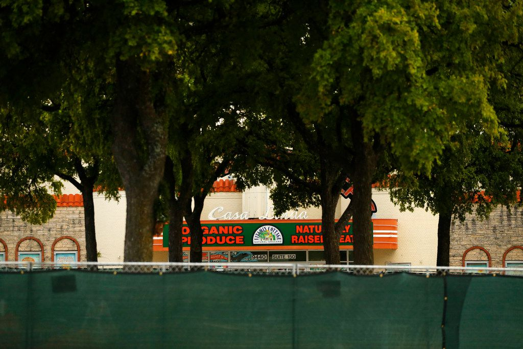 A fence surrounded a small grove of trees in the Casa Linda Plaza shopping center on July 27. There is a controversial decision to remove the historic trees to make way for more parking in the Dallas plaza. (Tom Fox/The Dallas Morning News)