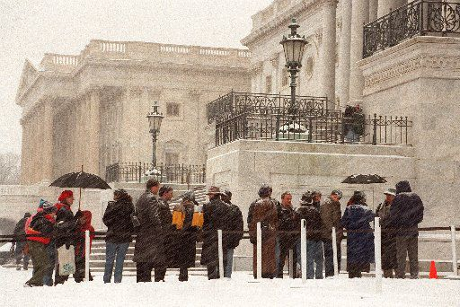 People line up in the snow outside of the U.S .Capitol Building in Washington, D.C., in hope of securing a ticket that will allow them  to watch the impeachment trial of  President Bill Clinton. Out of a total of 596 tickets only 50 are available to the public. The tickets expire daily and must be secured each day.