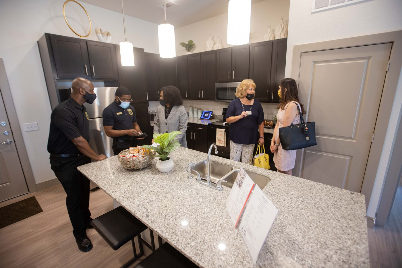 Palladium regional manager April West (center) leads a tour of a model apartment at Palladium RedBird apartments on Friday.