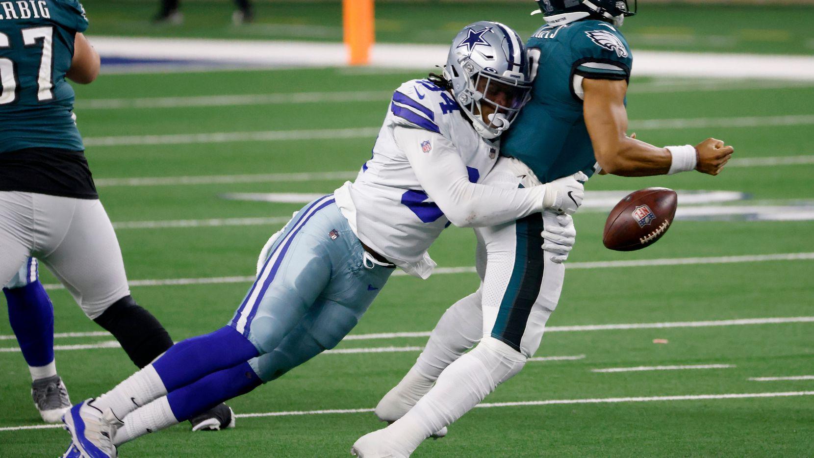 El mariscal de campo de los Eagles de Filadelfia, Jalen Hurts (der), suelta el balón cuando es capturado por el ala defensiva de los Cowboys de Dallas, Randy Gregory (izq) en el juego del domingo 27 de diciembre de 2020 en AT&T Stadium de Arlington