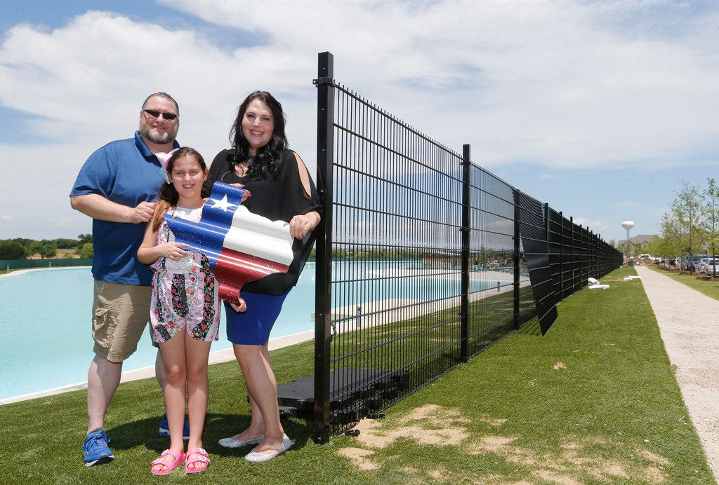 Scott and Marie Bailey, along with their daughter, Alexandra, in front of the Crystal Lagoon in Prosper. The Baileys, who moved from California to Texas about two years ago, built their home just across the street from the lagoon in Windsong Ranch.