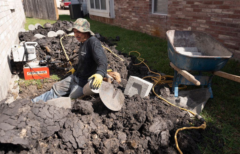 Ishmael Rangel, an employee with HD Foundations, drives concrete piers under a house the company is leveling in Mesquite on Tuesday.