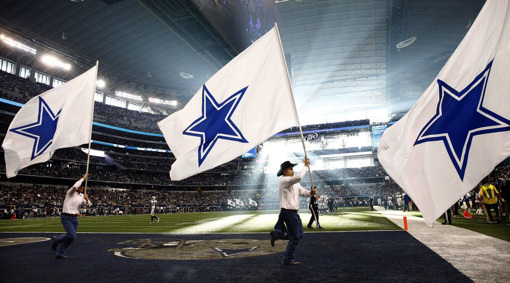 Dallas Cowboys spirit squad cary race across the field with flags after scoring on the Oakland Raiders in the first half at AT&T Stadium in Arlington, Thursday, November 28, 2013.