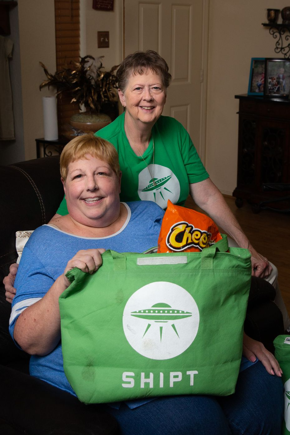 Sharon Fillner (left) and Deb Gardner, who works for the online grocery app Shipt, pose for a portrait in Fillner's home in Arlington, Texas, on July 24, 2019. Gardner has been shopping for Fillner for nearly 3 years because Fillner is homebound.