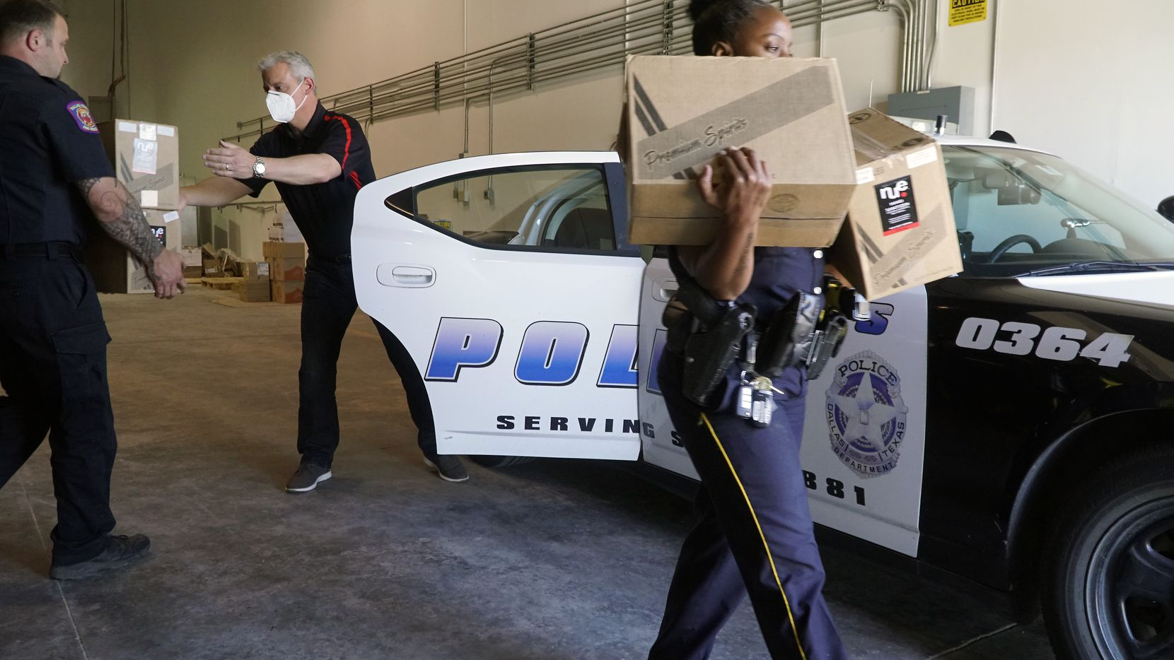 Southwest Spirits CEO Guillermo Rodriguez loads boxes of hand sanitizer into a patrol car at the County Warehouse in Dallas on Thursday. The company donated 10,000 bottles to first responders.