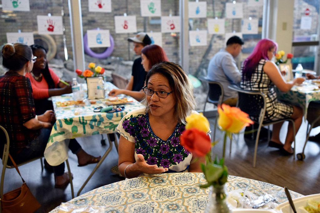 Gloria Lopez, chief executive officer of Trinity River Mission, sits with staff and volunteers during a luncheon hosted by the mothers of Trinity River Mission, Wednesday, Sept. 19, 2018 in Dallas. Every third Wednesday, mothers of the children enrolled at Trinity River Mission assist in the preparing and serving of a lunch to raise funds for the program.
