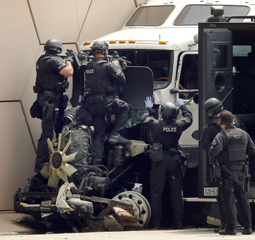 SWAT team members aim their weapons through the front windshield of semi truck that wrecked following a high speed chase on Interstate 30 at Cooper St. in Arlington  Friday, June 9, 2017. Other officers crawled into the truck and pulled a man out.. (Tom Fox/The Dallas Morning News)