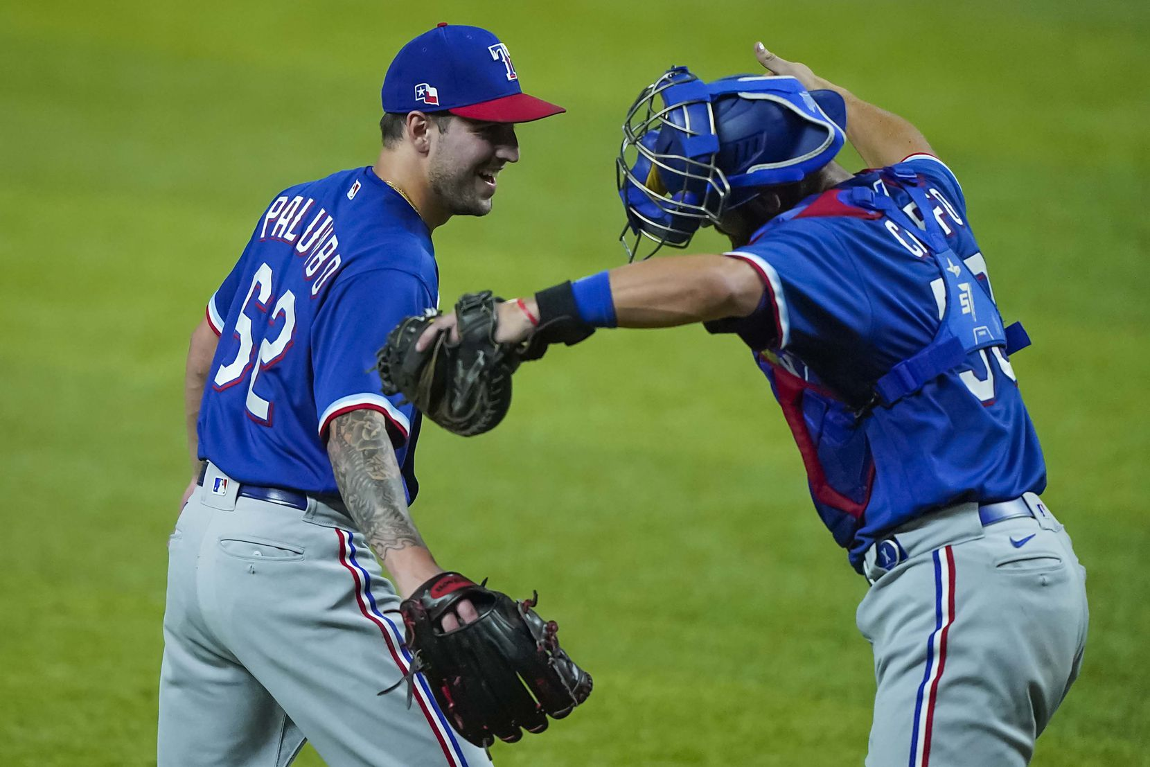 Pitcher Joe Palumbo playfully gets a distanced hug from catcher Nick Ciuffo after recording the final out in an intrasquad game during Texas Rangers Summer Camp at Globe Life Field on Thursday, July 16, 2020.