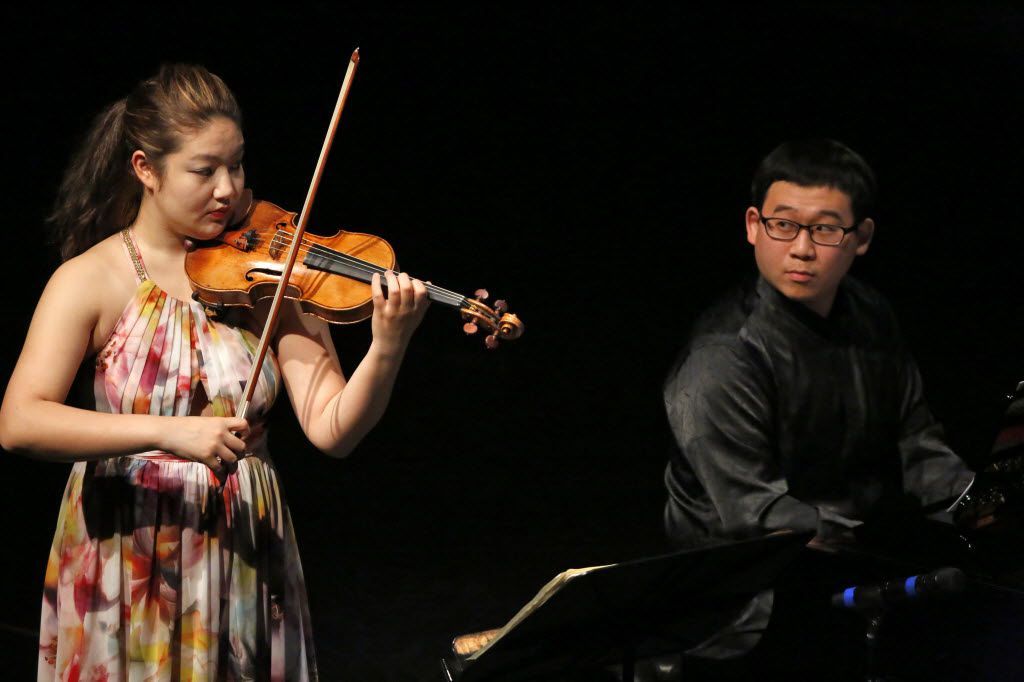 Jinjoo Cho plays violin and Hyun Soo Kim plays the piano as they lock eyes during Chamber Music International at Dallas City Performance Hall Friday May 22, 2015. (Nathan Hunsinger/The Dallas Morning News)