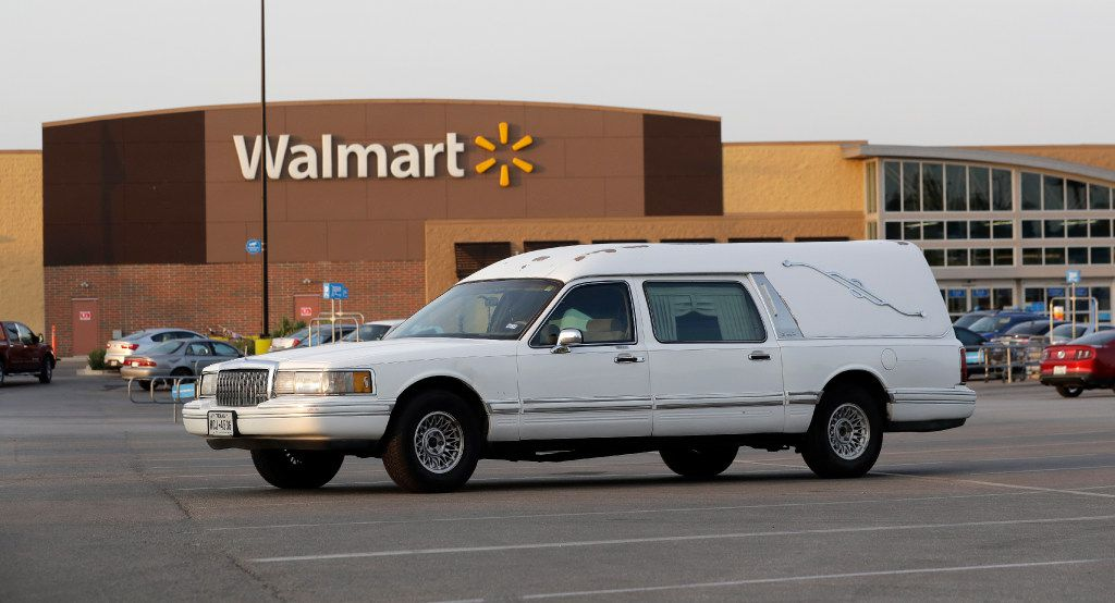 A hearse sits in the parking lot of a Walmart store where eight people were found dead in a tractor-trailer loaded with at least 30 others outside in stifling summer heat in what police are calling a horrific human smuggling case, Sunday, July 23, 2017, in San Antonio.