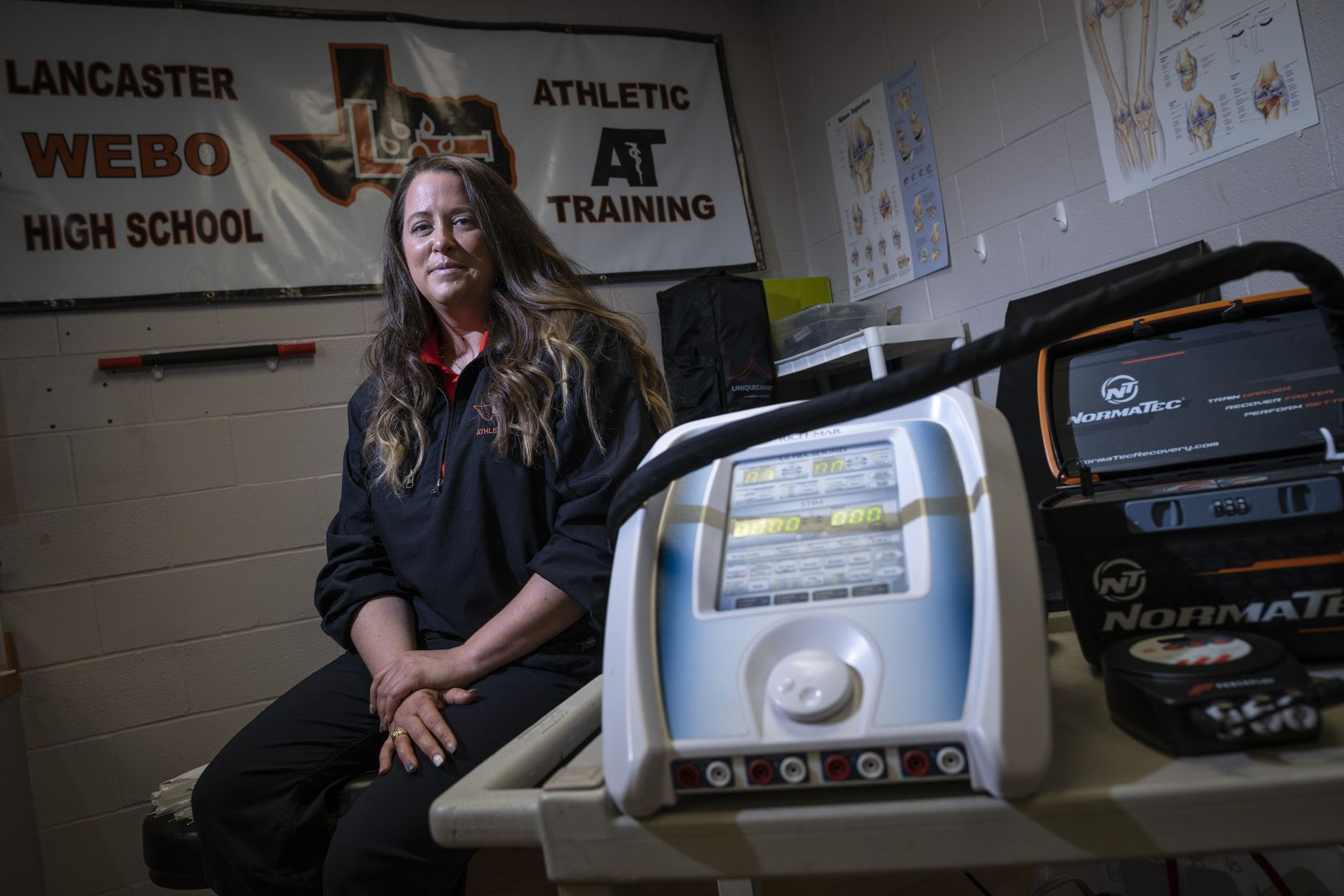 Jordan Hart, head athletic trainer for Lancaster High School, sits next to an ultra sound and electric stimulation device used on muscles, inside the school's athletic training room in Dallas, on Tuesday, March 09, 2021.