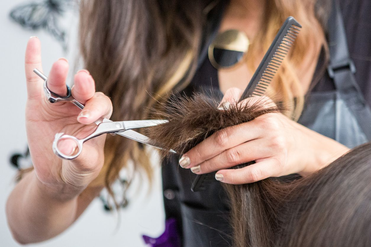 Una persona corta el cabello a un cliente en un salón de belleza.