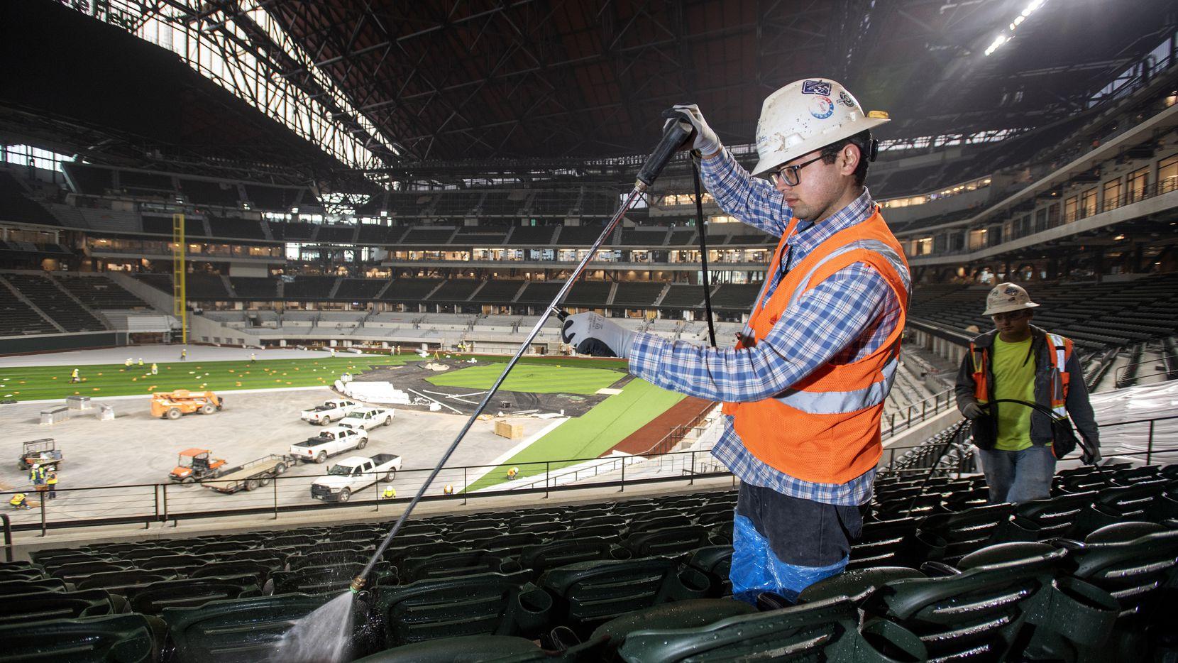 Cristian Zetino, de 22 años, limpia con una manguera a presión los asientos ya colocados dentro del Globe Life Field  de Arlington, la nueva casa de los Texas Rangers. Al fondo se ve a José Zetino, de 23 años, hermano de Cristian.