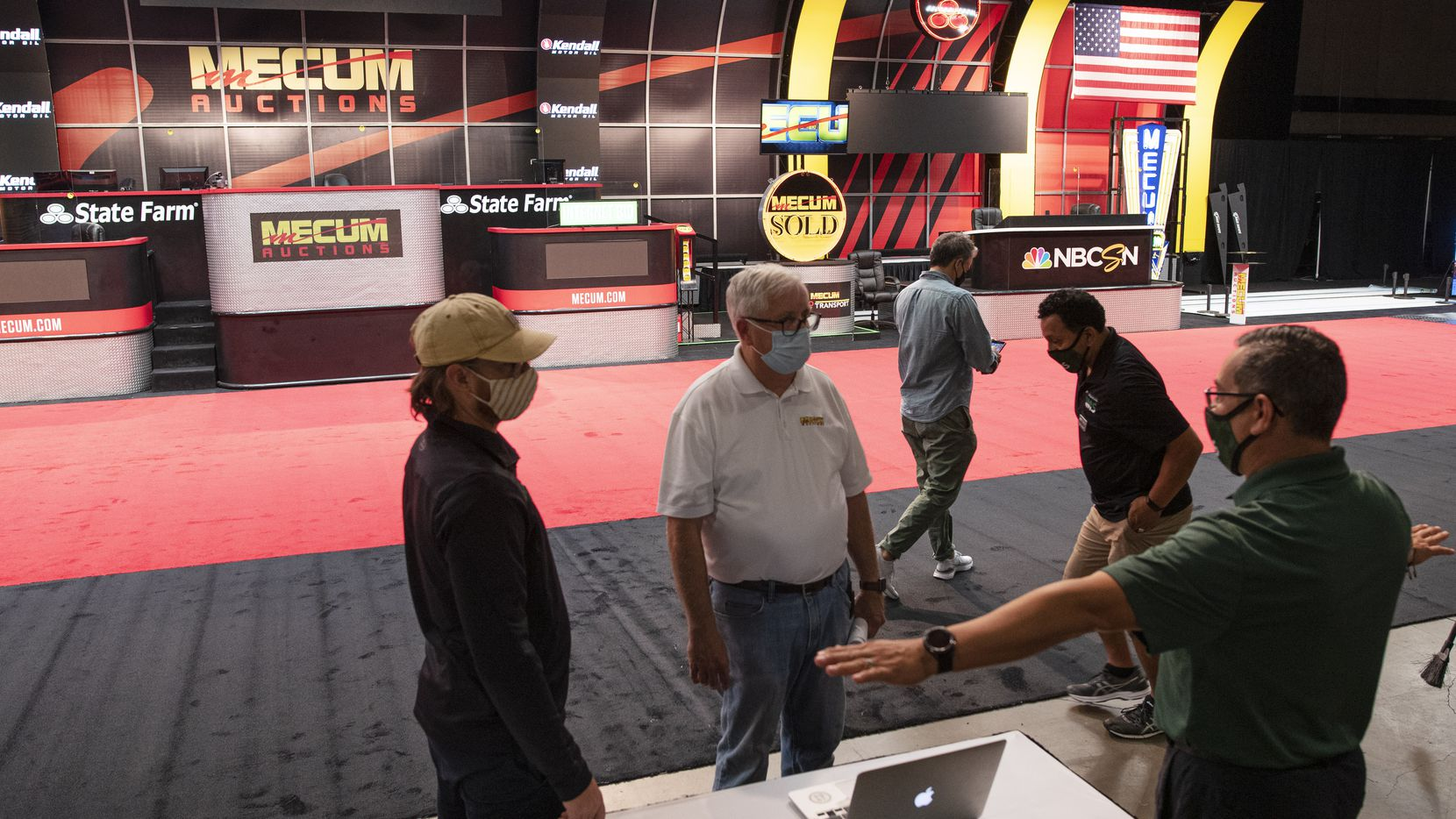 Greg Stone, left, and Hugo Gonzalez, far-right, both of Inclusive Management Services, speak with Harold Gerdes, center, Vice President of operations for Mecum Auto Auction, as they work together to prepare the main stage for the Mecum Auto Auction at the Kay Bailey Hutchison Convention Center in downtown Dallas, Oct. 13, 2020.