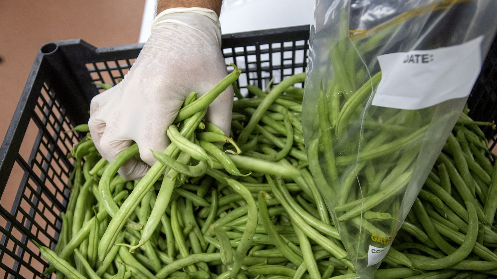 Garry Abbs, an instructional specialist of hospitality management at the Dallas College Culinary, Pastry and Hospitality Center, measures out green beans to be included in boxes of ingredients that will be picked up and used at home by students who are continuing classes online due to the coronavirus.