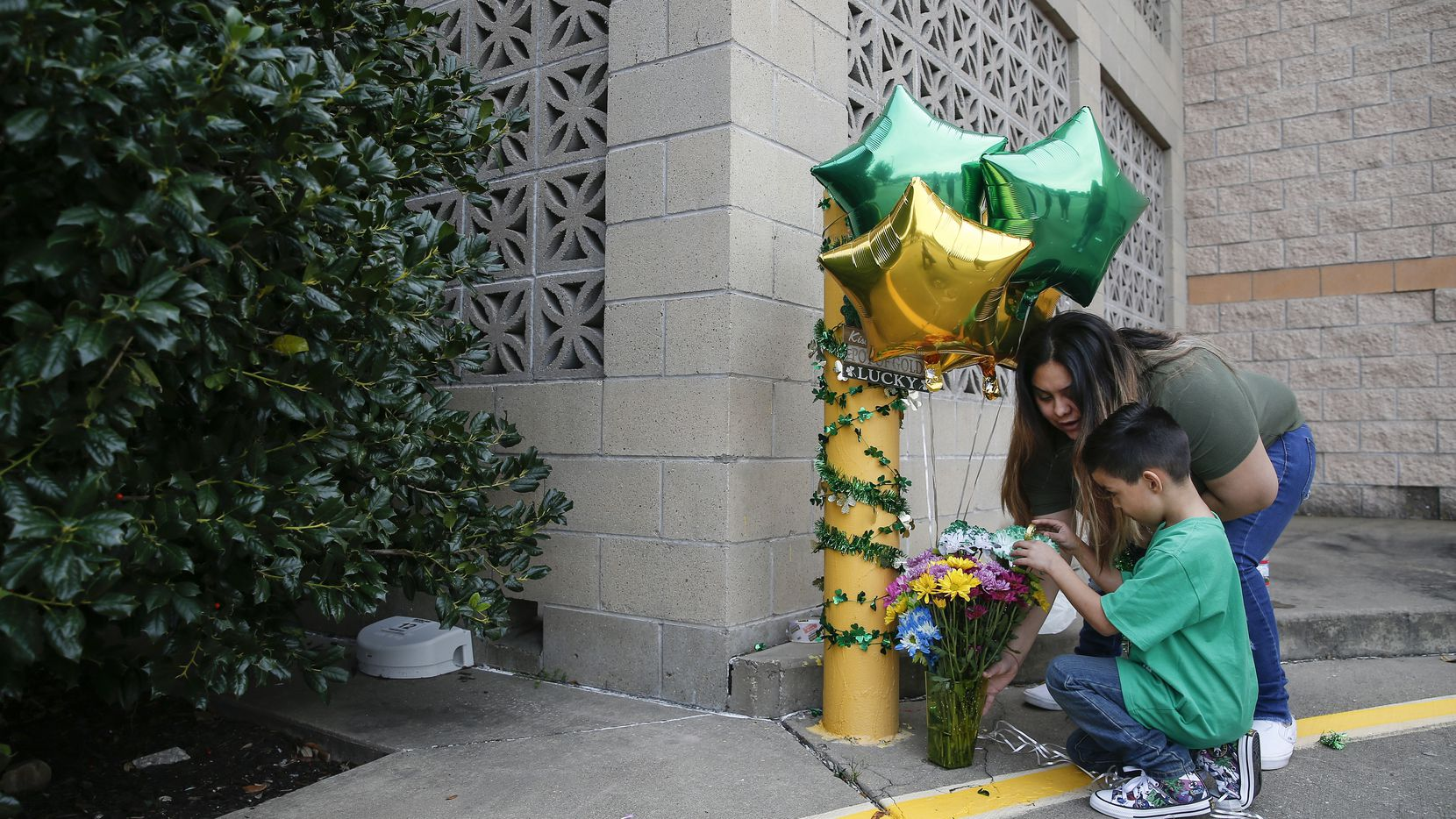 With the help of her brother, Joel Guerrero, 6, Destiny Rangel, who was best friends with Emily Bingabing, who was killed outside a Walmart in Far North Dallas in late January, decorates a memorial near the location of the homicide on Saturday, Feb. 22, 2020 in Dallas. Rangel says they plan to continue decorating the location once a month. (Ryan Michalesko/The Dallas Morning News)