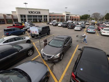 A patron pushed a shopping cart through the parking lot of Kroger at Mockingbird and Greenville in March.