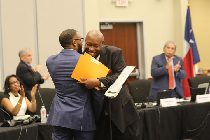 Dallas ISD trustee Maxie Johnson (right) hugged fellow trustee Justin Henry after being sworn in Thursday.