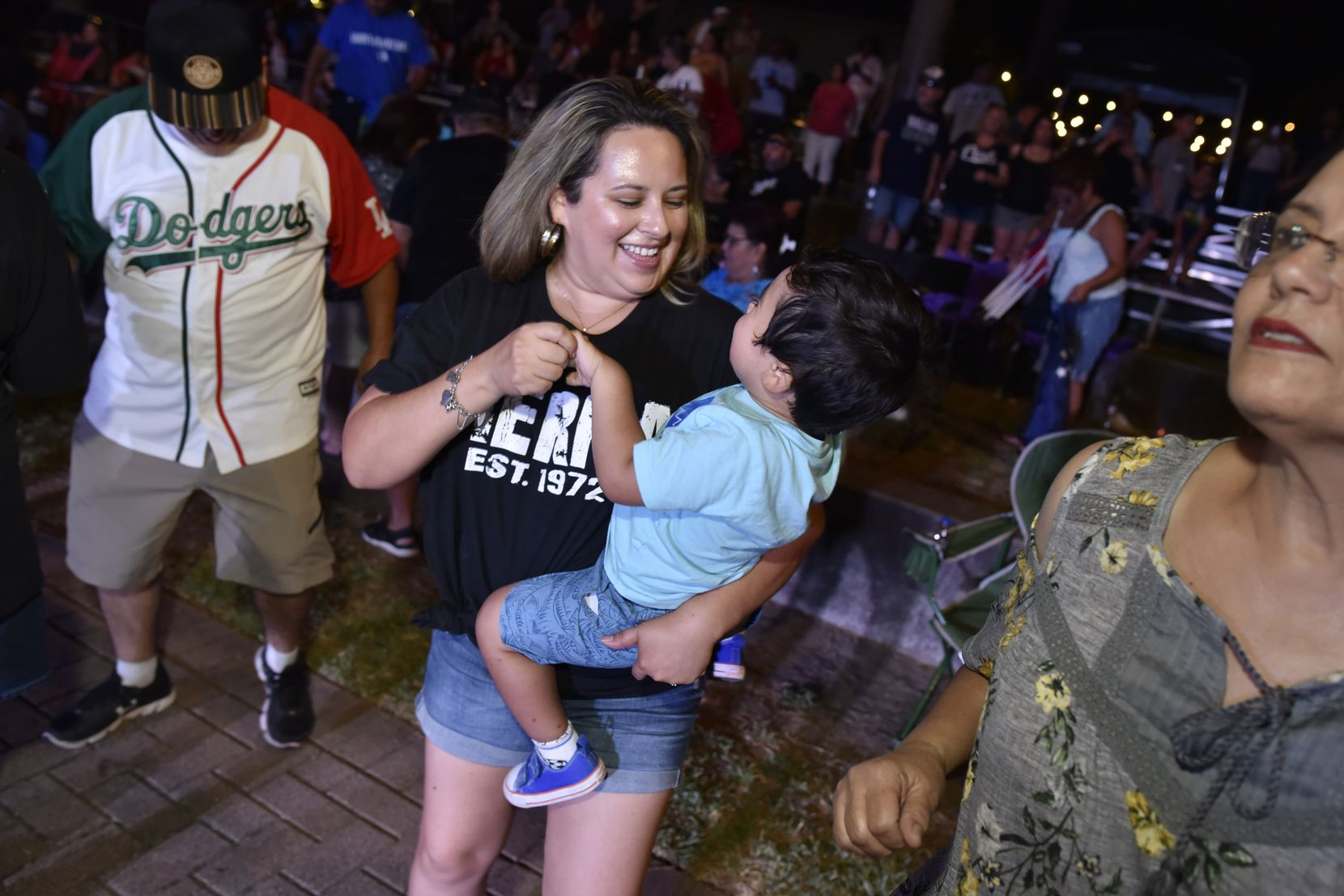 A woman dances with a child to the sounds of Los Angeles band Tierra during the 2019 Latino Heritage Festival in DeSoto.