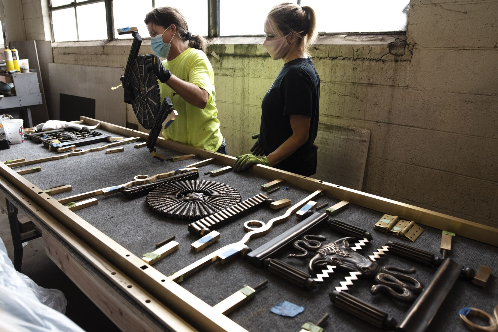 Restoration technicians Allison Savage (left) and Jessica Thomas work on pieces of bronze artwork that are part of the Hall of State's decorative door grilles.