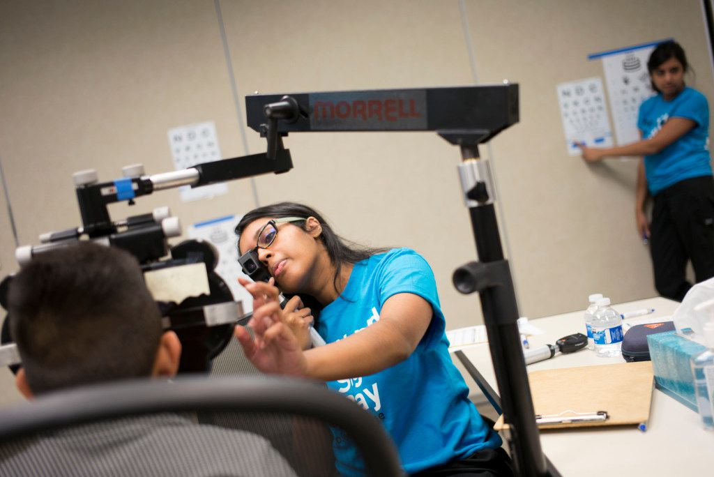 Volunteer Ashley Varghese (center) exams a Carrollton ISD student's eye during the free eye exams provided by Essilor Vision Foundation during World Sight Day  at Essilor of America on Oct. 13, 2016 in Dallas, Texas.