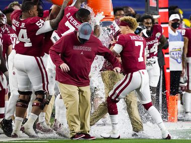 Oklahoma quarterback Spencer Rattler (7) holds onto head coach Lincoln Riley as he is doused with the water bucket in the closing seconds of a victory over Florida in the Cotton Bowl Classic at AT&T Stadium on Wednesday, Dec. 30, 2020, in Arlington. (Smiley N. Pool/The Dallas Morning News)