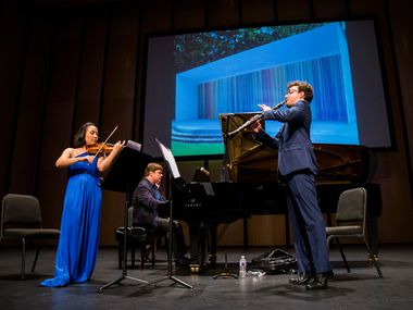 Violinist Grace Kang Wollett, pianist Mikhail Berestnev and clarinetist Danny Goldman rehearse under a photo of art by Ian Davenport before a Basically Beethoven Festival concert on July 7, 2019 at Moody Performance Hall in Dallas.