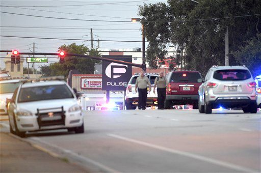 Tres vehículos de la policía y otros autos cerca del centro nocturno Pulse Orlando, al fondo, luego de una balacera mortífera la mañana del domingo 12 de junio de 2016,./AP