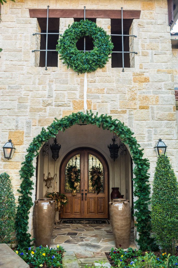 A wide, bold garland on a stone archway, along with a coordinating wreath, creates a timeless statement and defines the entrance to this home.