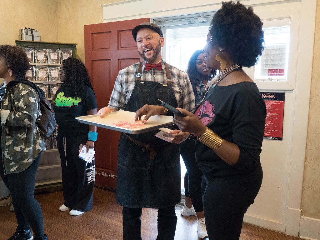 Clyde Greenhouse, owner of Kessler Baking Studio (center) hands out samples to attendees of the Soul of Dallas Bus Tour in Oak Cliff area of Dallas.