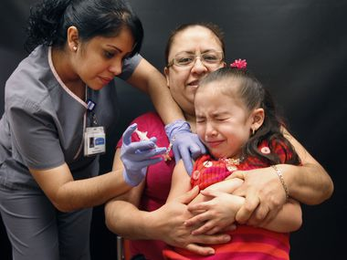 Maria Sanchez, center background, from Dallas, holds her daughter Kamila Rodriguez as Kamila gets a flu vaccine from a medical assistant Isabel Castruita at MyChildren's Pediatric Practice in Garland, TX on January 22, 2013. (Kye R. Lee/The Dallas Morning News)