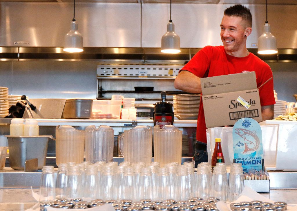 Corey Ahrens, 37, restocks condiments at Fish City Grill in Richardson.