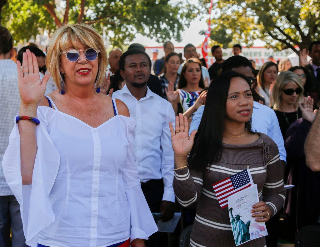 Alta Shafaian-Fard, left, originally from South Africa, and Ruby Vargas, from the Philippines, take the oath of citizenship to become U.S. Citizens at the Plano International Festival Saturday October 14, 2017. The event was held at Haggard Park in downtown Plano, Texas. (Ron Baselice/The Dallas Morning News)