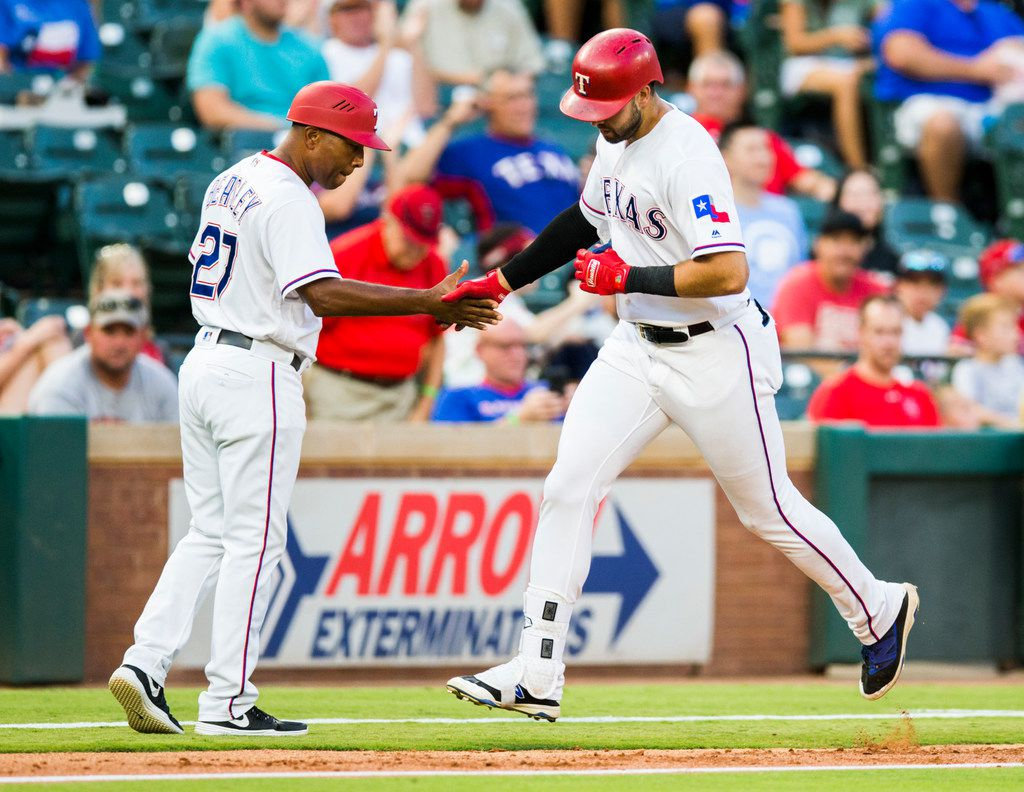 Texas Rangers out fielder Joey Gallo (13) gets a high-five from third base coach Tony Beasley (27) as he makes his way home after a home run hit during the first inning of an MLB game between the Texas Rangers and the Los Angeles Angels on Thursday, August 16, 2018 at Globe Life Park in Arlington. (Ashley Landis/The Dallas Morning News)