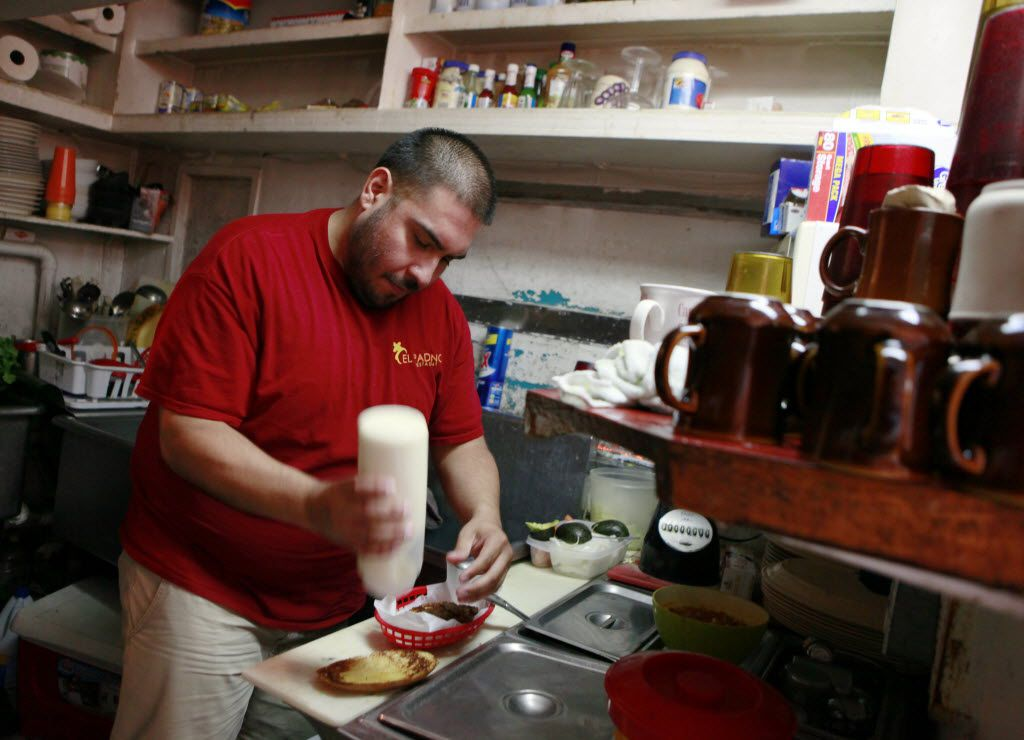 Co-owner of El Padrino restaurant Juan Contreras Jr., prepares a sandwich for a customer while working at the Jefferson Boulevard location, on Thursday, July 23, 2015 in Dallas.