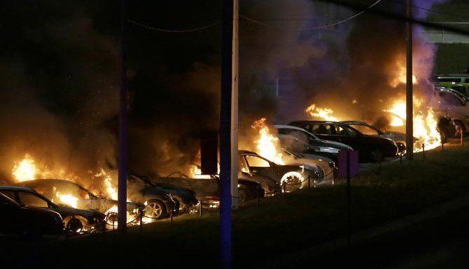 Autos arden en llamas en una agencia de vehículos en Ferguson, Missouri, la noche del lunes, cunado autoridades revelaron que no fincarán cargos al policía que mató a un adolescente afroamericano en un enfrentamiento. El anuncio desató saqueos, vandalismo y protestas violentas. (AP/CHARLIE RIEDEL)