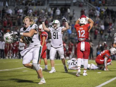 Southlake Carroll defensive linemen Travis Keener (34) and Calder Bray (91) celebrate after a missed 29-yard field goal attempt by Rockwall-Heath preserved a 36-35 Dragons' victory as time expires on a high school football game at Wilkerson-Sanders Stadium on Thursday, Sept. 2, 2021, in Rockwall. (Smiley N. Pool/The Dallas Morning News)
