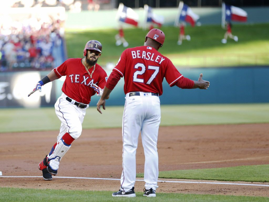 Texas Rangers second baseman Rougned Odor (12) celebrates with Texas Rangers third base coach Tony Beasley (27) as he rounds the bases after hitting a solo home run in the second inning off of Cleveland Indians starting pitcher Corey Kluber (28) on opening day at Globe Life Park in Arlington on Monday, April 3, 2017. (Vernon Bryant/The Dallas Morning News)