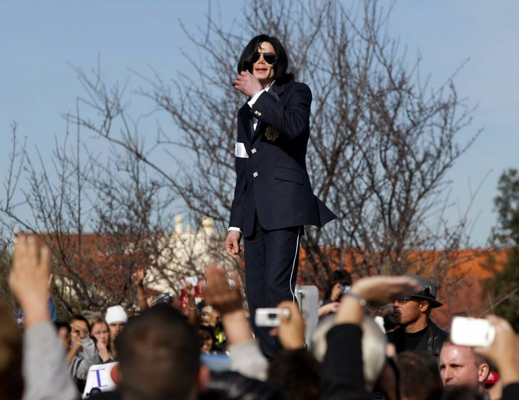 In this Friday, Jan. 16, 2004 file photo, Michael Jackson waves to his fans from atop his limousine after his arraignment on child molestation charges at the courthouse in Santa Maria, Calif. AP Photographer Nick Ut will be retiring from the AP in March 2017 after 51 years of taking photographs from the front lines of the Vietnam War to the red carpets of Hollywood.