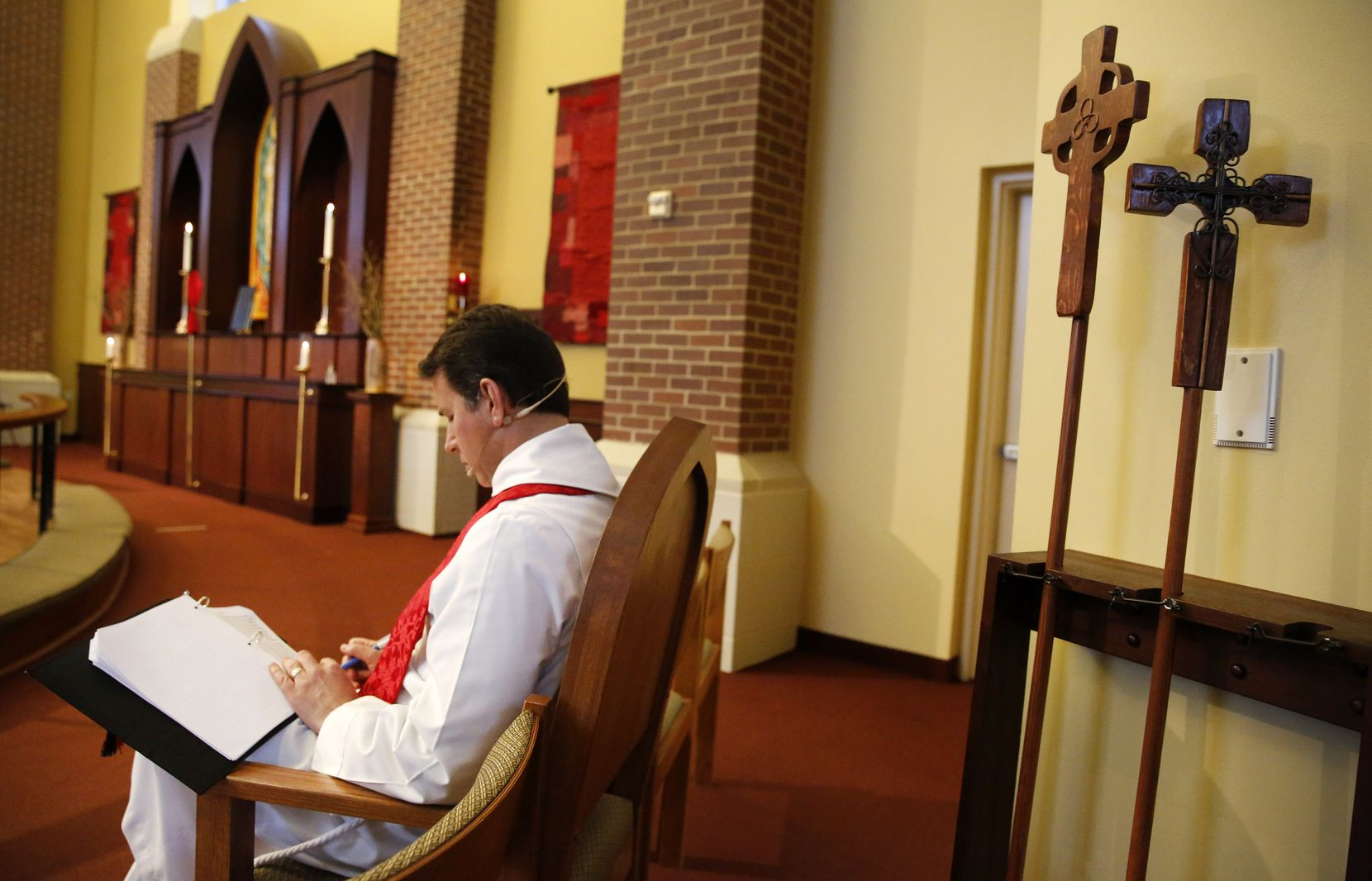 Father Clayton Elder looks over the online schedule for their Holy Thursday service and washing of the feet. (Tom Fox/The Dallas Morning News)