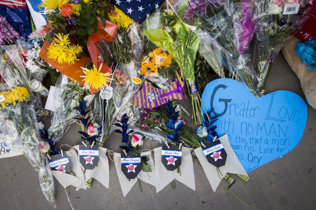 Flowers bearing the names of five fallen peace officers rest with other messages of support for law enforcement in a growing memorial outside the Dallas Police Department headquarters in Dallas.