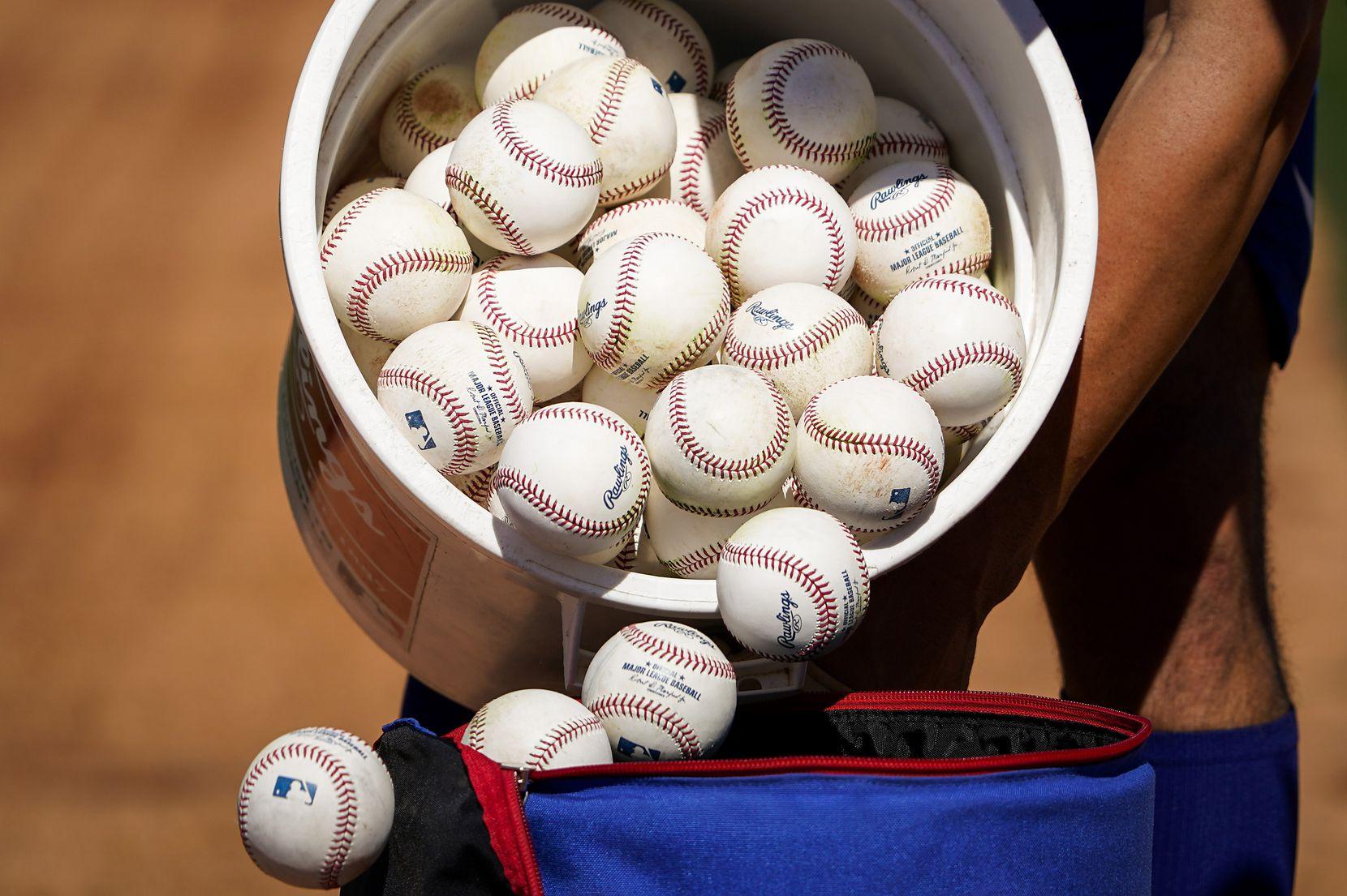 Rangers infielder Greg Bird dumped a bucket of baseballs from infield practice into a bag as spring training got underway in February in Surprise, Ariz.