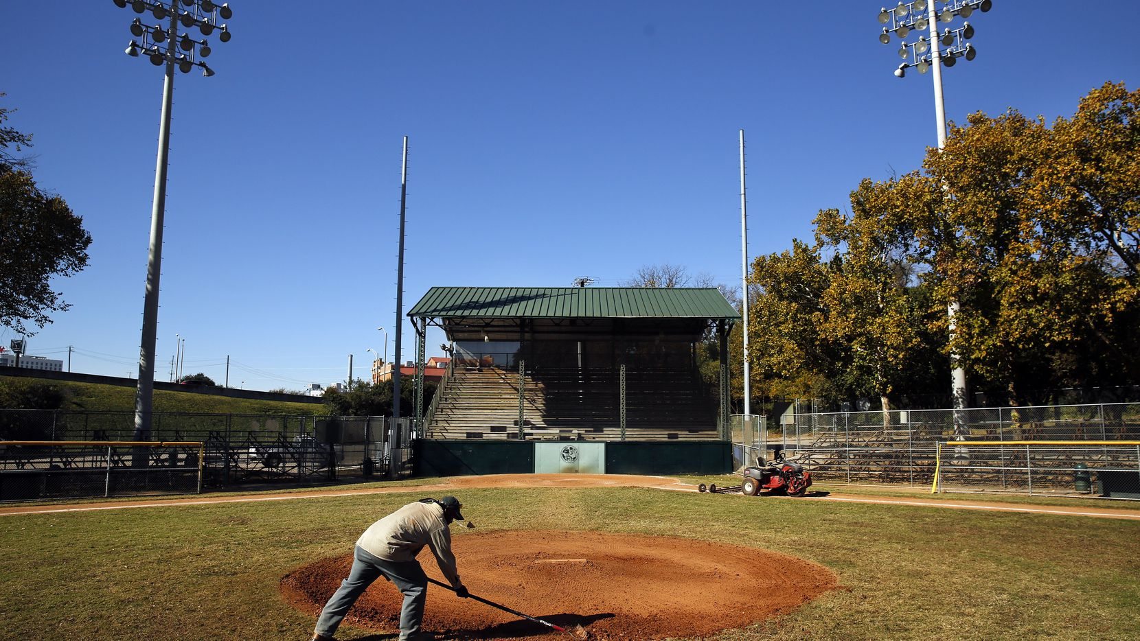 Lawrence Willie, a Dallas Park and Recreation Department employee, fixes holes in the pitching mound at the historic but dilapidated baseball field at Reverchon Park.