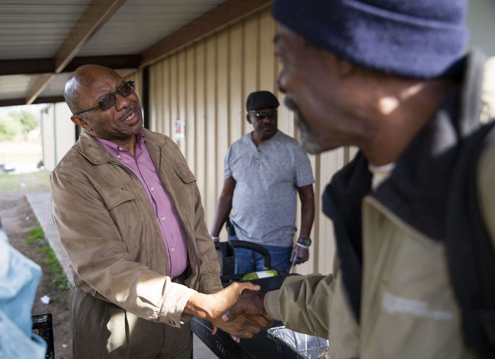 Pastor Chris Simmons (left) of Cornerstone Baptist Church in Dallas greets people as they leave the church's community kitchen.