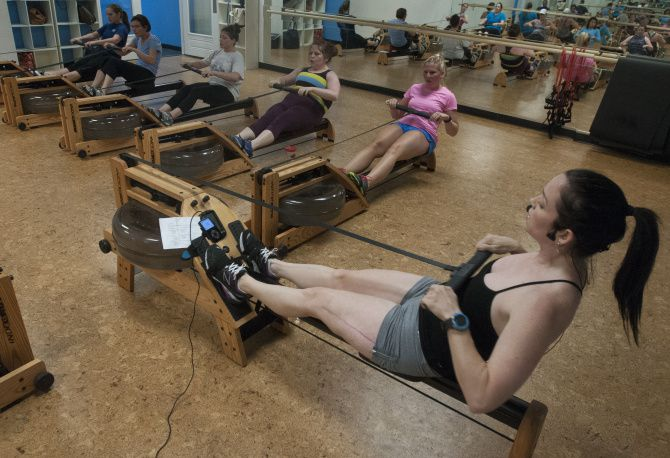 Karen Soltero, co-owner of Crowbar Cardio, teaches a rowing class.  After she started the business with a childhood friend she contracted a flesh eating bacteria that almost took her life.