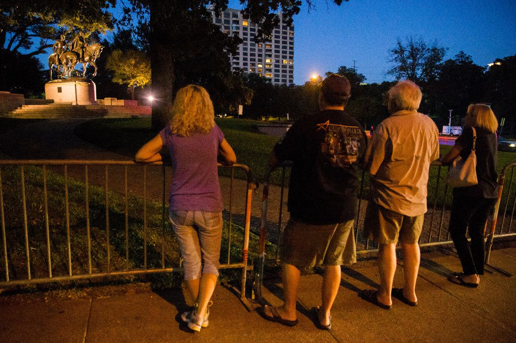 People look at a statue of Robert E. Lee just after 8 p.m. on Wednesday, September 6, 2017 at Robert E. Lee Park in the Turtle Creek area of Dallas. (Ashley Landis/The Dallas Morning News)